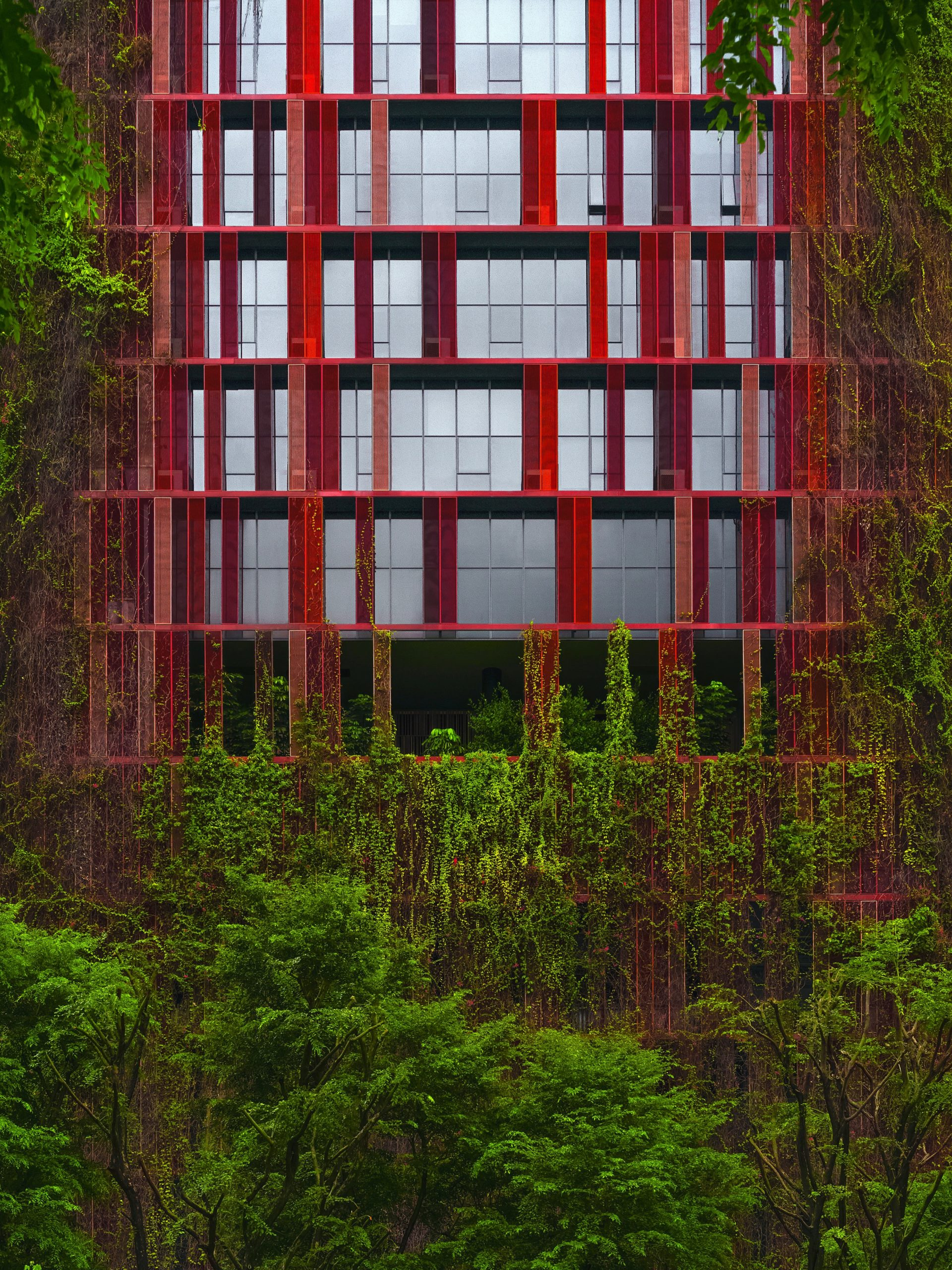 Rotes Gebäude, das mit grünen Pflanzen bewachsen ist